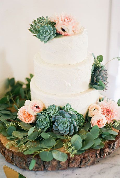 White Cake with Succulents & Roses. A three-tiered white wedding cake decorated with greenery, succulents, peonies, ranunculus, and dahlias arranged by florist Lilla Bello.