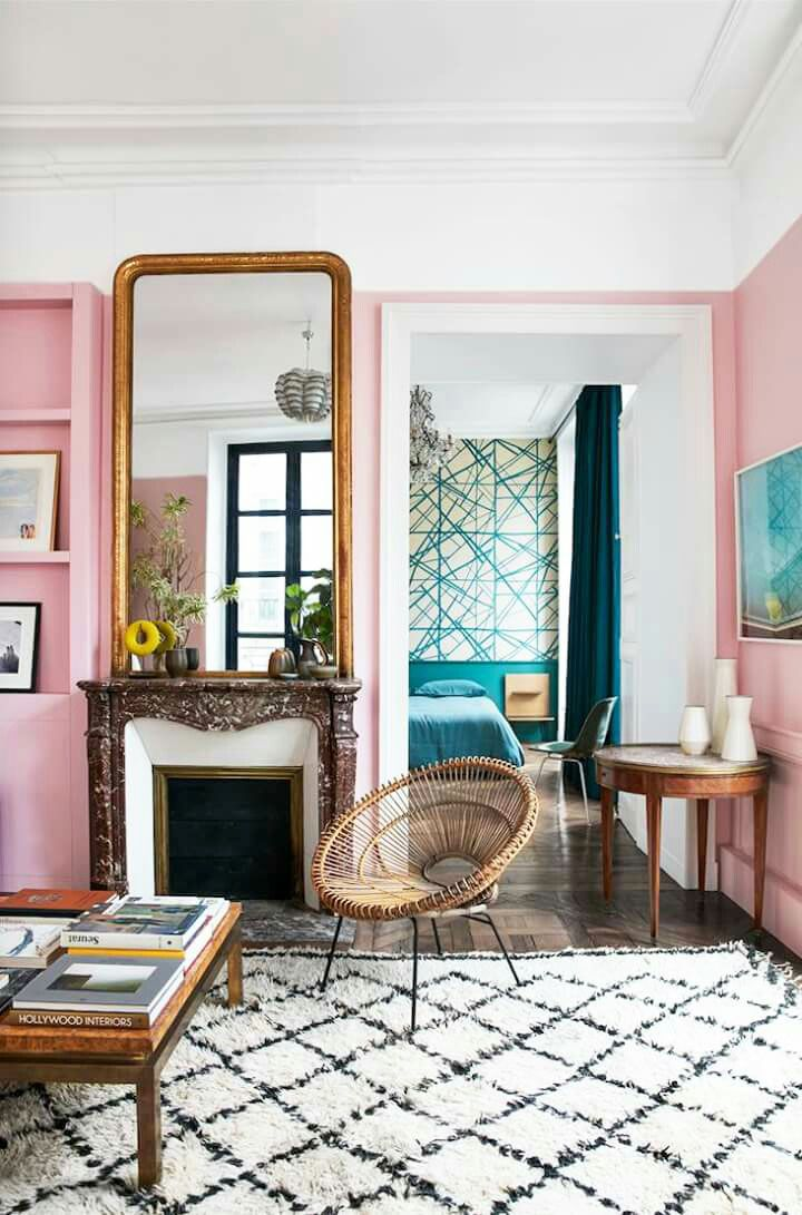 Pink parisian living room with gold mirror ornate fireplace and pink walls