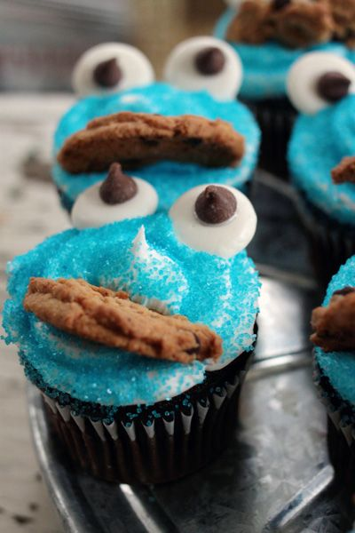 Great Birthday cupcake idea. Blue sprinkles is way better than blue icing... would be a good activity for young kids to put eyes and cookie in the icing!