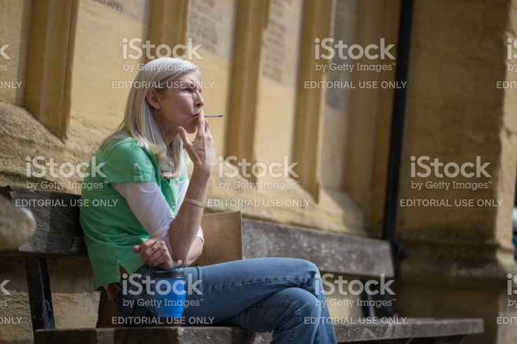 Woman inhaling deeply on a cigarette sat next to St John the Baptist Church in Cirencester Town centre royalty-free stock photo