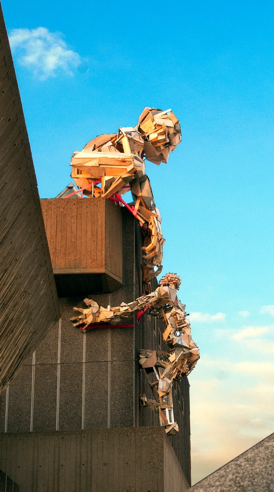 A pair of huge wooden puppets, on the side of the Hayward Gallery, South Bank, London in 2013