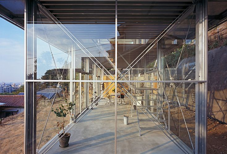 HOUSE IN ROKKO/ by Tato Architects/ Yo Shimada/ Kobe/ Japan/  image © ken'ichi suzuki/ A 3.5 meter by 13.5 meter  plane is secured for the foundation, requiring manual digging from the nearby breast wall to hold back the earth's soil. Resting above the  concrete pad, the two-storey steel structure forms an open, glass-enclosed ground level and private upper level clad with metal panels.