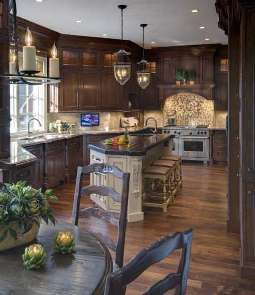 A traditional kitchen with cherry cabinets and a cream painted island.