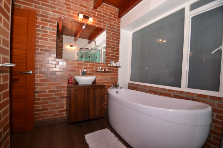 Bogota extreme home make over...after the AptsColombia renovation superb rustic brick ensuite bathroom with tub www.aptscolombia.com