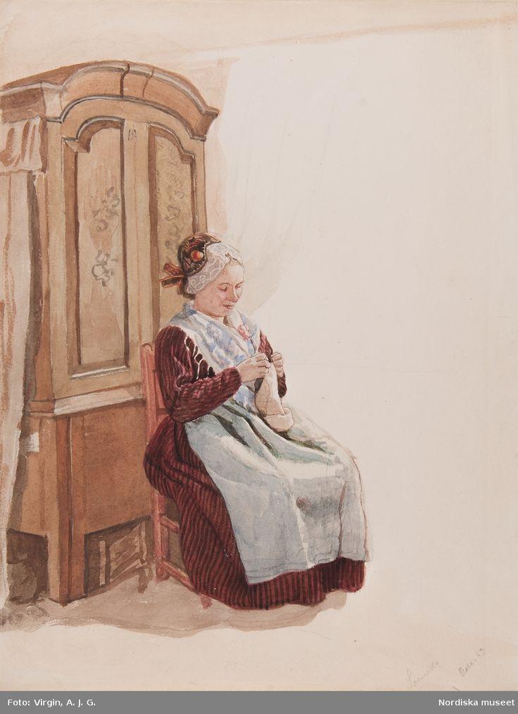 Dräkt. Handarbetande kvinna i helfigur sittande  framför ett skåp. Akvarell. Sorunda, Södermanland, Sweden