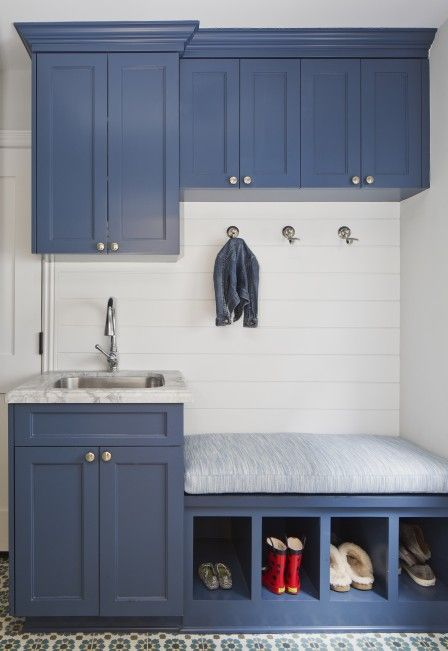 Simply gorgeous blue mudroom features a blue washstand fitted with a marble top holding a stainless steel sink with a polished nickel gooseneck facuet.