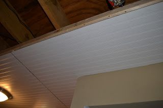 Basement Ceiling Installation -- Blogger says they used Liquid Nail on the floor joists and a tack gun with a compressor to install. Beadboard comes in 4 x 8 sheets where wall paneling is located. You can caulk the seams... Or cover seams with plastic strips with a sticky back (plastic strips used to seal the exterior of a bathtub and the floor... they cut it in half)