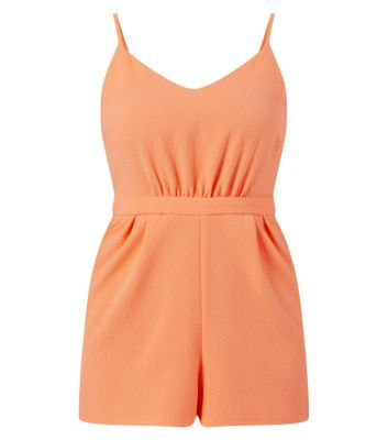 Work this vibrant strappy playsuit with nude caged wedges for a feminine.