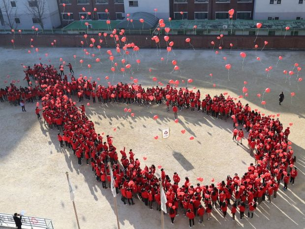 South Korean students form the shape of the red ribbon in Seoul, South Korea. (Lee Jin-man/Associated Press)