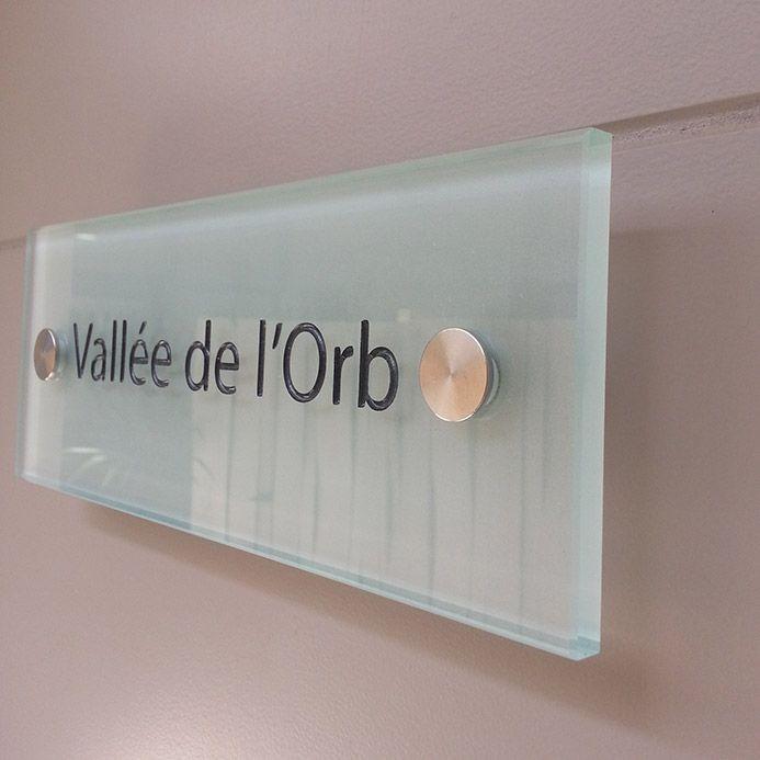 Plaque signalétique en verre d'intérieur sur porte pour la signalisation de salles, bureaux, ou autres services de lieux publics ou privées.