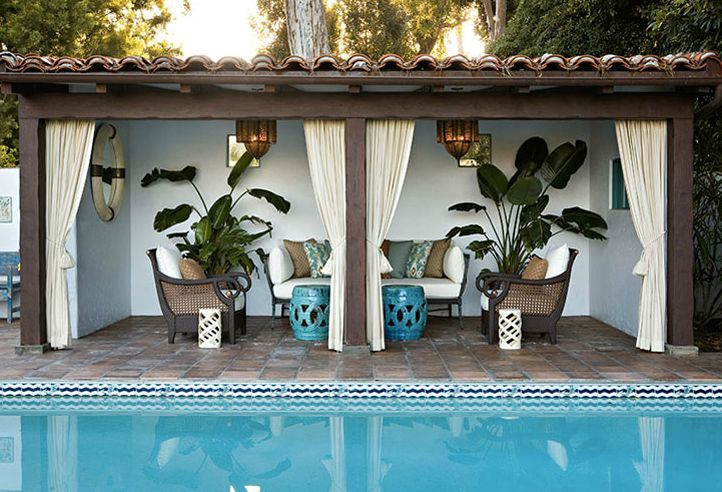Lovely pool cabana with ivory outdoor curtains, turquoise blue rope stools, outdoor sofa & chairs and ikat pillows.