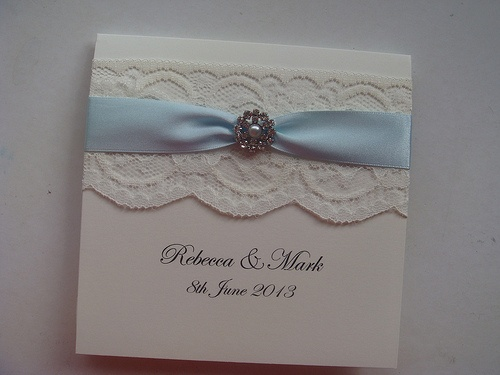 Vintage wedding invitation in blue with pearl, lace and satin ribbon
