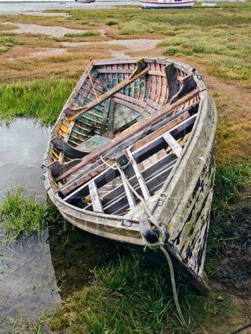 A derelict old wooden fishing boat lying on rough grass at Alnmouth, Northumberland, UK