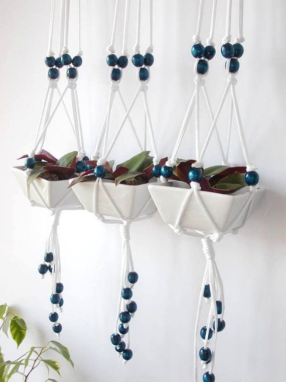 Set of three beaded macrame plant hangers is made from white 3mm durable Polypropylene braided cord and dark blue wooden beads. It can be used