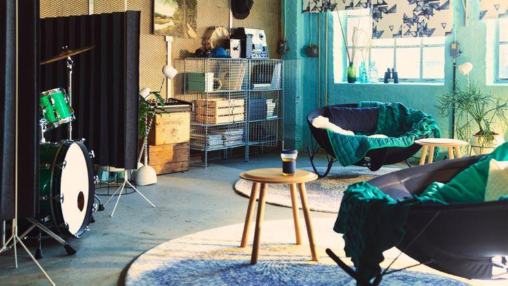 Estancia con dos modernas mecedoras redondas de color negro con colchas verdes y dos mesas auxiliares de haya. De fondo, dos soluciones de almacenaje de acero galvanizado con revistas de música y discos antiguos.