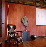 Axel Vervoordt | The Interior Archive: the torso of an Asian sculpture stands between an antique leaver wing-backed chair and a painting by Lucio Fontana.