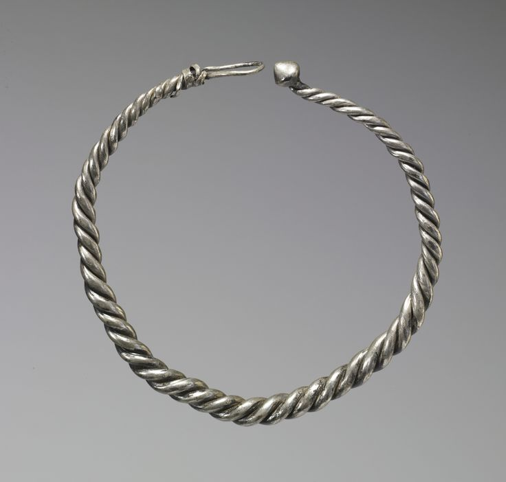 This Viking (late 9th-10th century) neck ring is made from three twisted silver wires and is fastened by an unusual conical knob and loop clasp. It was both jewelry and money to its owner. Large neck rings and smaller arms rings were buried in Viking hoards in Ireland, Scandinavia, and England, all important hubs of Viking sea trade. This neck ring was found buried with a plain arm ring (present location unknown), in Fenit, County Kerry, Ireland in the late 1800s.