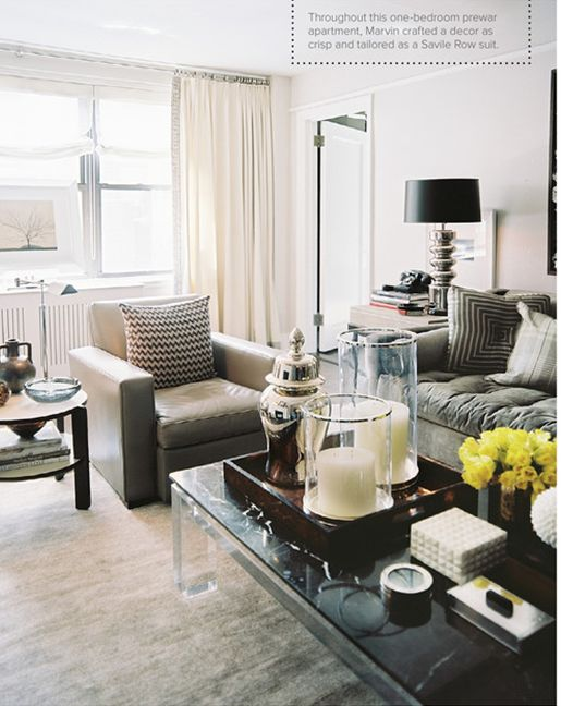 """masculine glamour"" small living room oversized everything. mirror glass candles green as an accent in a white grey and black living room"