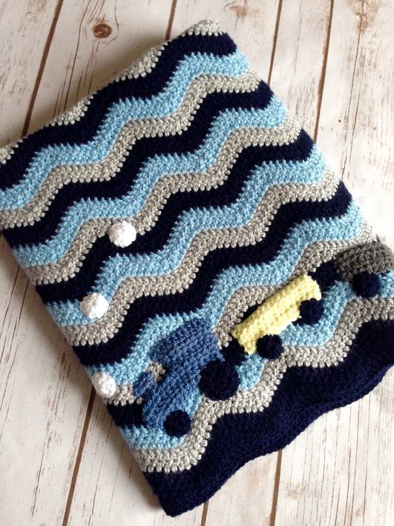 Train blanket crocheted in beautiful Midnight blue, Cloud blue and silver. Added appliqué train detail. Made to order using beautiful soft Aran yarn, this snuggly baby blanket is perfect from new baby to toddler and beyond. Your little one will want to keep and treasure this blanket forever. This would make a wonderful baby shower gift or the perfect addition to any baby boys nursery!  Machine washable and dryer safe too this blanket is practical as well as lovely to look at and snuggle…