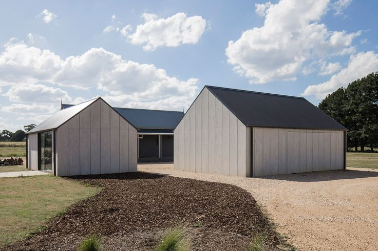 Adam Kane has added a garage and painting studio to a house in Australia, which features pitched corrugated-metal roofs and pared-back interiors.