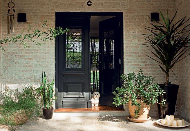 De estilo inglês, a porta antiga de duas folhas de madeira entalhada deu ar imponente à entrada da casa. Comprada em uma loja de demolição, a porta recebeu pintura automotiva preta durante a reforma do imóvel, há três anos, p contrastar com as paredes de tijolos à vista e esbranquiçados. Com 1,60m de largura e 2,20m de altura, uma porta como esta, de madeira entalhada, envernizada ou pintada, sai p R$6mil na Pinho de riga antiguidades. O hall tem piso de fulget e vasos c plantas da Anni…
