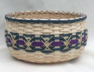 """INFINITY-""""Begin with a round wooden base for this elegant snack basket with decorative sets of X's.  The majority of the basket is start/stop weaving.  Shaping is emphasized in the pattern and you will do the Triple X rim lacer in matching waxed linen.  Also the decorative X's in the center with chair caning.  Choose two colors ~ color choices listed at the top of the page.  Dia:  10""""  H:  5-1/2"""""""