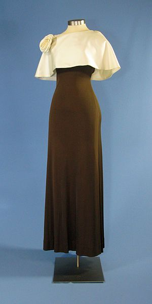A formal dress with a cape designed by Luis Estevez for First Lady Betty Ford. The dark brown, jersey gown features a white cape and a train down the back. In addition, it also has a white flower on the shoulder, no sleeves, and a zipper up the back. Designed by Luis Estevez in 1975.  Mrs. Ford wore this dress on October 27, 1975 during a State Dinner with President Anwar Sadat of Egypt.