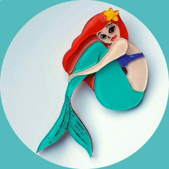 This little mermaid brooch, is made from several layers of laser cut, high grade acrylic. Each layer has been hand-painted and carefully assembled to give each brooch a unique dimensional effect. The brooch is coated in a clear, crystal resin to give a glossy finish, a metal brooch clasp is attached and then the brooch is polished and packaged beautifully and individually for safekeeping. Add a unique twist to any outfit. Perfectly pairs with girly, vintage, pin-up or rockabilly style…