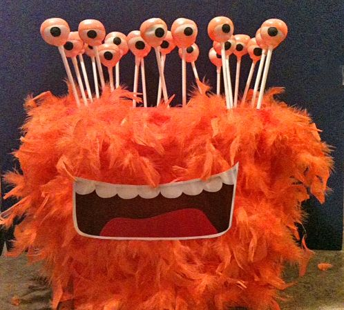 """Monster Head Cake Pop Stand ~ fluffy feather boa + a big old block of styrofoam + lots of hot glue + an """"oh so cool"""" cut-out mouth = fun cake pop stand perfect for eyeballs"""