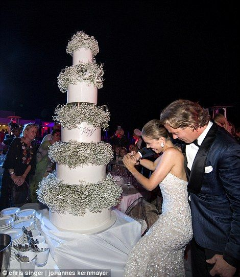 The bride and groom cut into their impressive five-tier cake, which was adorned with green and white flowers