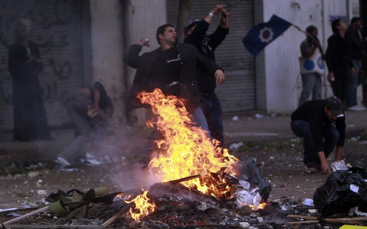Protesters throw stones at army soldiers at the cabinet near Tahrir Square in Cairo