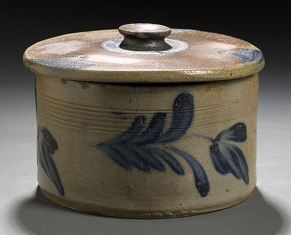 """American, third quarter 19th century. A lidded salt glazed butter crock having incised decorative bands, perimeter decorated in tulips; lid decorated with three hearts; all in brushed cobalt; 4.5"""" high x 7"""" diameter."""