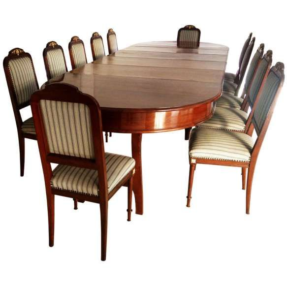 Antiga mesa de jantar para doze convivas, em MOGNO MACIÇO. Estilo inglês VITORIANO, século XIX. Quatro pernas torneadas, amarração em xis, e mais duas pernas de cavalete para total extensão.Ornamentos em bronze, polidos: Ornatos no espaldar das cadeiras, rosetas e arremates nos flancos.Medidas mesa aberta: 80 x 365 x 130 cm. e 80 x 272 x 130 cm. Medidas mesa fechada: 80 x 174 x 130 cm. Medida das cadeiras: 100 x 44 x 43 cm.