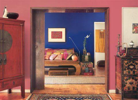 Uma cama de madeira, antigamente usada para fumar ópio, serve de marquesa, a...