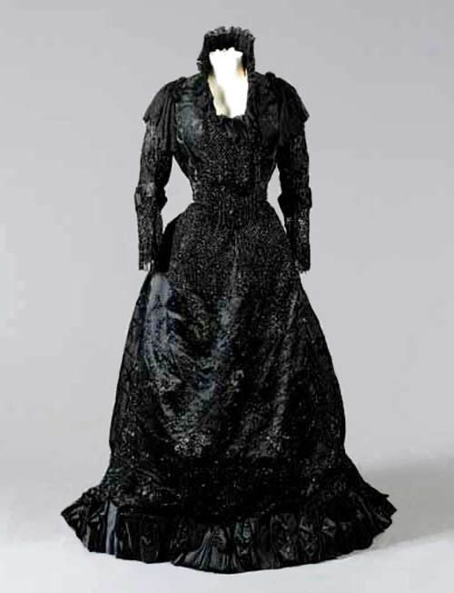 ~E. Pingat black damask satin ball gown, ca. 1888. Bodice and skirt heavily embellished with jet beaded roses and latticed fringed panels. Trained skirt with pleated satin bands~   Sotheby's