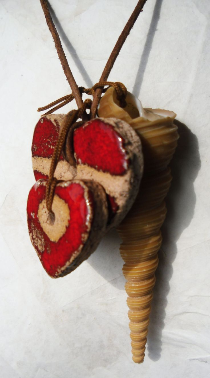 Necklace: 2 glazed ceramic handmade hearts, a shel and leather cord.