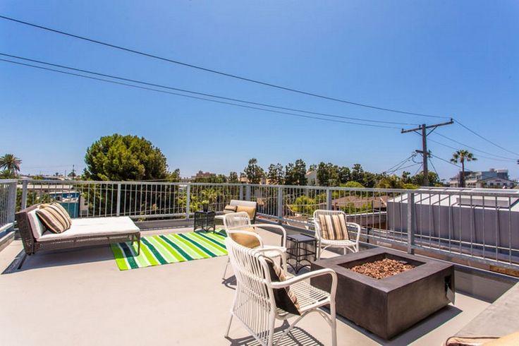 terrasse moderne avec tapis extérieur, lit de jour design, chaises en bois massif et parement en béton