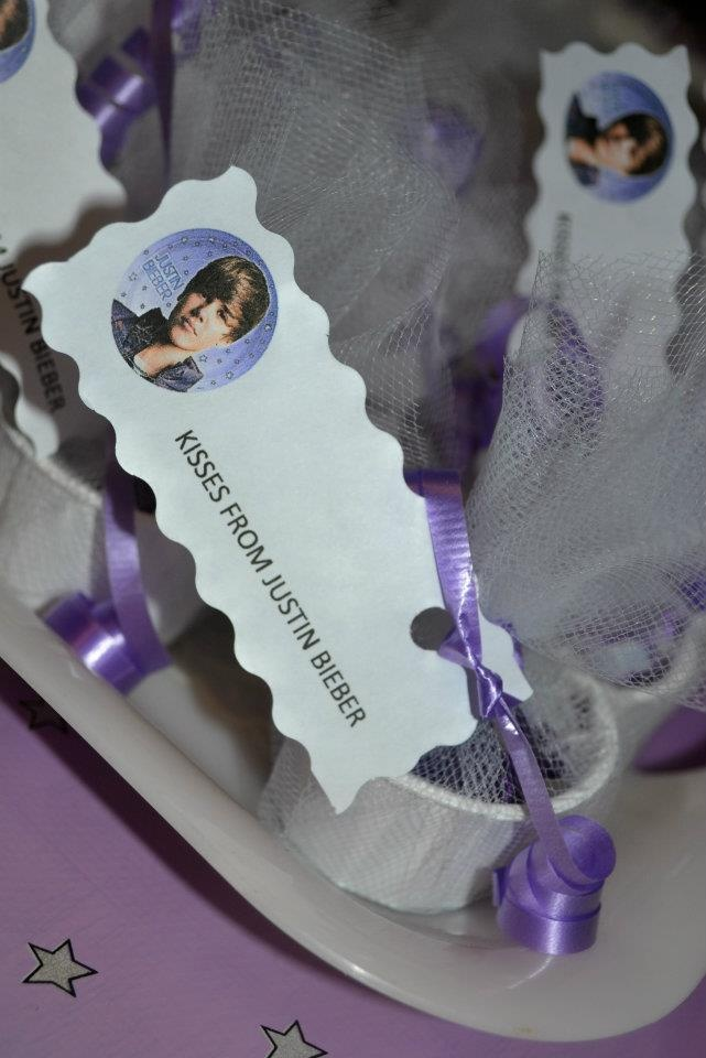 "I filled up a tiny jello shot like cup full of Hershey Kisses (Silver and Purple) for my daughter's birthday party, wrapped in tulle, tied with matching curling ribbon, and put ""Kisses From Justin Bieber"" (since that was the theme) but you could use any photo and character. The kids thought it was super cute!"