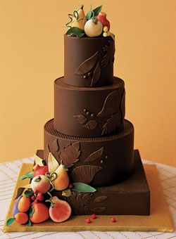 A chocolate cake iced with ganache and decorated with rolled chocolate and marzipan fruit is a perfect complement to an orange color scheme.  Cake by Cheryl Kleinman.