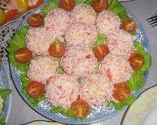 """Закуска """"Рафаэлло""""  Ингредиенты:  - Сыр - 200 г  - Яйца - 4 шт.  - Чеснок - 3-4 зубчика (20 г)  - Крабовые палочки - 1 упаковка (200 г)  - Майонез - 3 ст. л. (100 г)  - Салатные листья (для подачи)  Приготовление:  1. Яйца отварить вкрутую и натереть на мелкой терке.  2. Добавить сыр, натертый на мелкой терке.  3. Добавить чеснок, выдавленный через пресс, и майонез. Хорошо перемешать.  л..."""