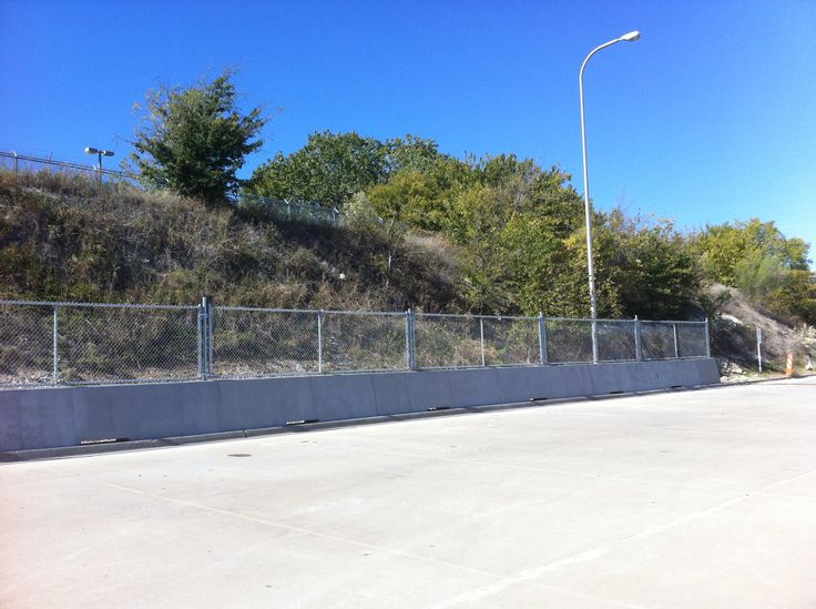 Chain link fence on top of concrete wall. Installed by