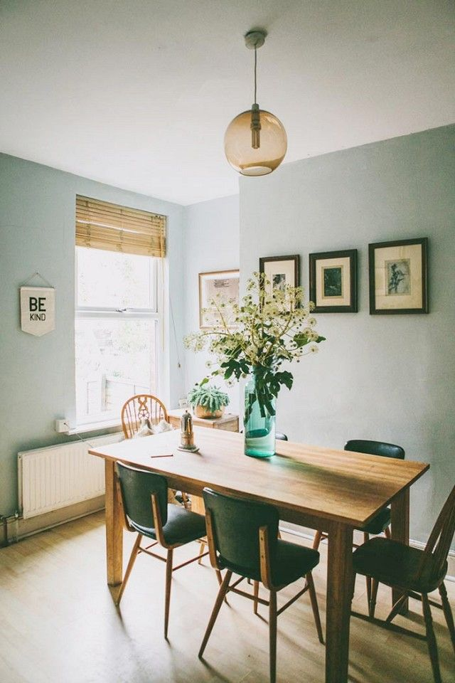 Dining room with refreshing cool blue-gray walls, and a blush glass pendant light