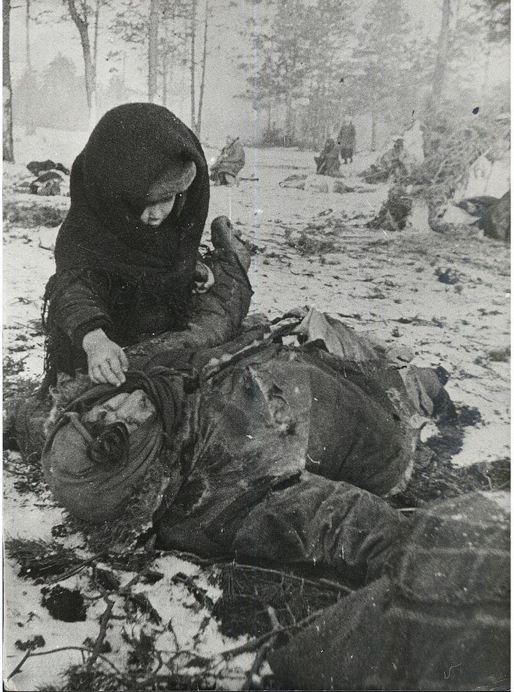 March 1944: A child in the Ozarichy hostage holding camp tries to wake up his mother, who has been murdered by the Germans. Ozarichy in Kalinkovichy region of Belarus was large fenced-in area on the German front line holding local civilians as human shields against Soviet attacks. The hostages were left without shelter, food, and water and were decimated by exposure, gunfire, and hunger. When Soviet troops finally defeated the Germans in the area, they found 15,960 children among the…