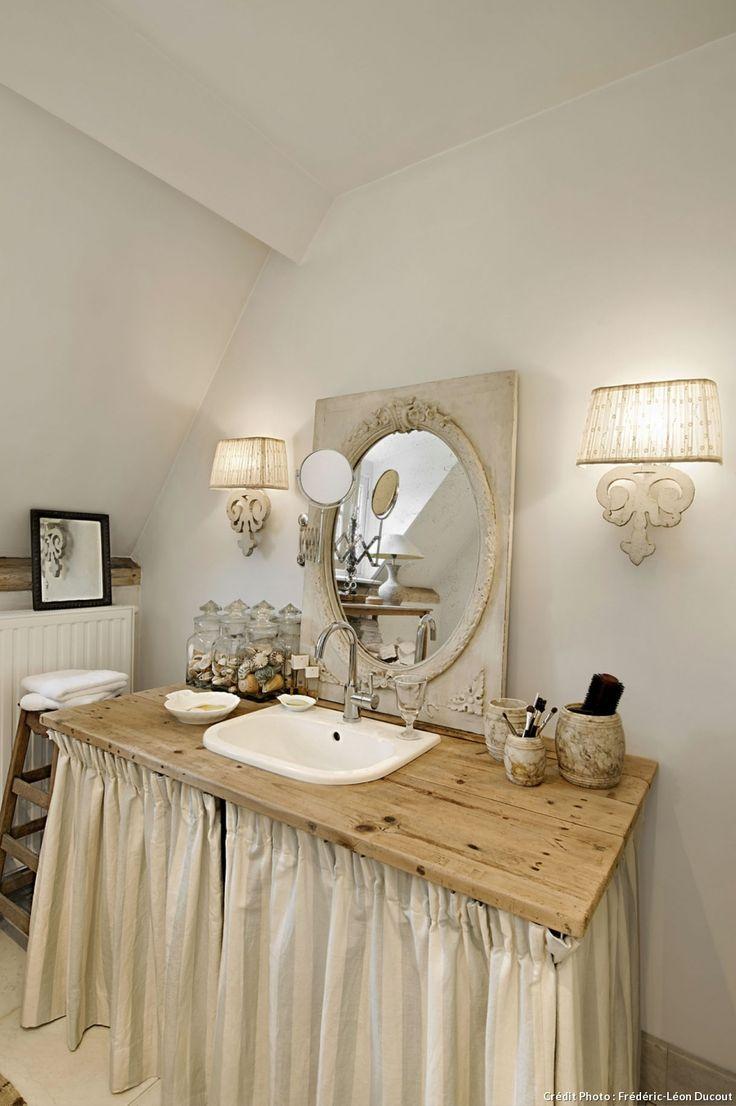 Le charme suranné d'un lavabo tout simple avec son plan de travail habillé de tissu juponné pour cacher les étagères.