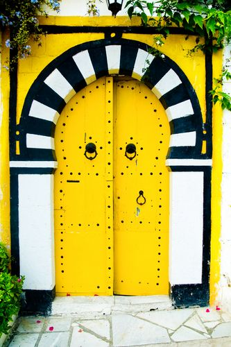 I heart this bright yellow (and black and white) painted door found in Tunisia!