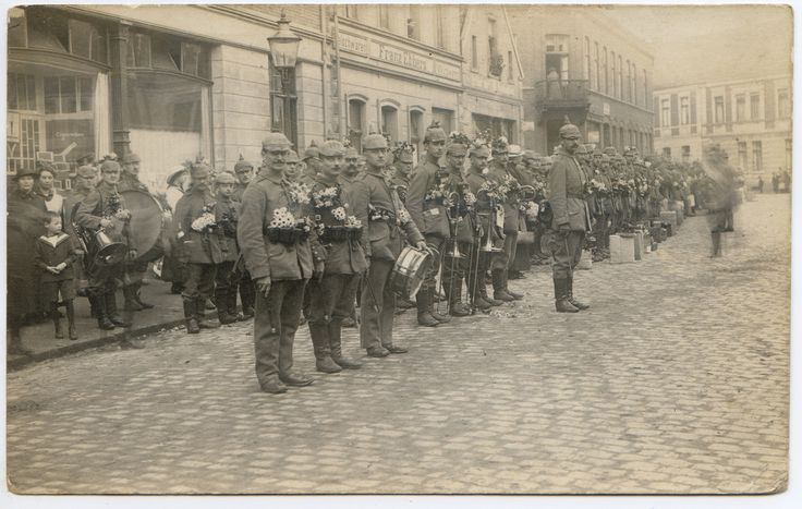 """Spalier des 5. Lothringischen Infanterie-Regiments Nr. 144 (IR 144) auf dem Marktplatz in Ahaus. Das Bild zeigt eine Truppenverschiebung am 12. Juni 1915.  Von links sind die Häuser Bügener-Nacke mit dem Tabakwarenhandel Stamm, die  Metzgerei """"Fleischwaren - Franz Ebbers- Wurstwaren"""", die Westfalia-Drogerie Engels, Elektro-Lampe und die Lederwarenhandlung Lorenz an der Marktstraße zu erkenne.   siehe dazu: Auszug aus dem Fleischerei-Adressbuch von Deutschland, Band II, 1925 Ahaus: E..."""