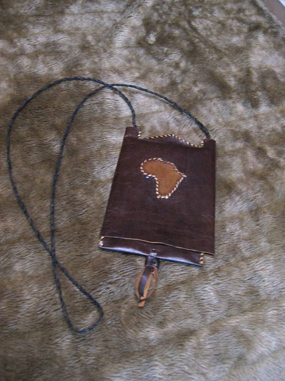 someone put a lot of great stitches and ideas into this unique crossbody money pouch. flat and rigid, the top sleeve slides up to reveal the pouch underneath. The cover has a replica of what I believe to be the continent of Africa. there are no makers marks. Measures 5x8 inches.
