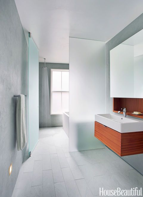 A plane of frosted glass separates the wet side of the bathroom, with the open shower, from the dry side, with the sink. Hansgrohe's Downpour 180 showerhead makes you feel as if you're standing under a water fall. Vero sink by Duravit. IMO faucet by Dornbracht. Towel bar by Samuel Heath.