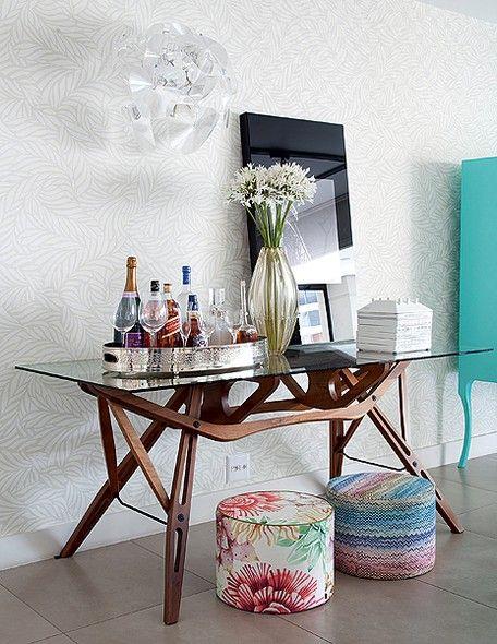 As bebidas ficam mais sofisticadas na bandeja de prata. No móvel azul-turquesa, ao lado, ficam as taças e copos. Sob o aparador, estão dois pufes, que podem ser usados como assentos extras no living. Projeto da arquiteta Tininha Loureira