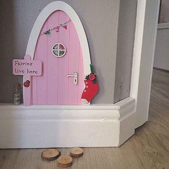 Let a some magic into your home and capture your little one's imagination with our beautiful handmade wooden fairy doors. Put your door on a skirting board, wall or even on a shelf (because fairies can fly of course!)  Made from sustainably-sourced birch plywood, painted in a gorgeous blossom pink colour and decorated with fabric bunting, a window, door handle and personalised signpost. Suitable for indoor use only. The door doesnt open (as only the fairies can do this).  The door measures…
